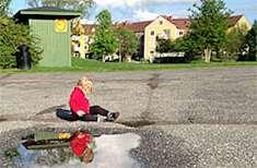 Barn leker vid tom plaskdamm vid Stjärnhusen