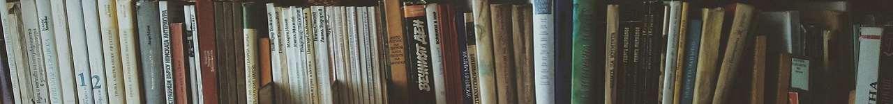 En hyllplan fylld med böcker med ryggen utåt.