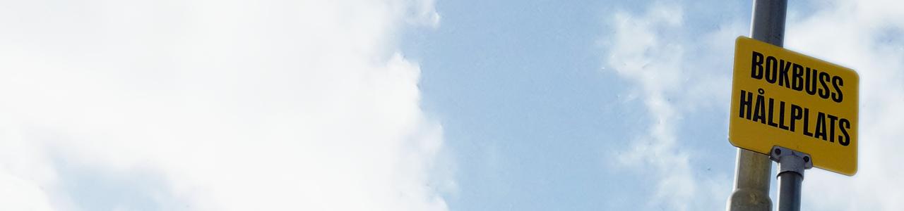 En av bokbussens hållplatsskyltar med en klar himmel i bakgrunden